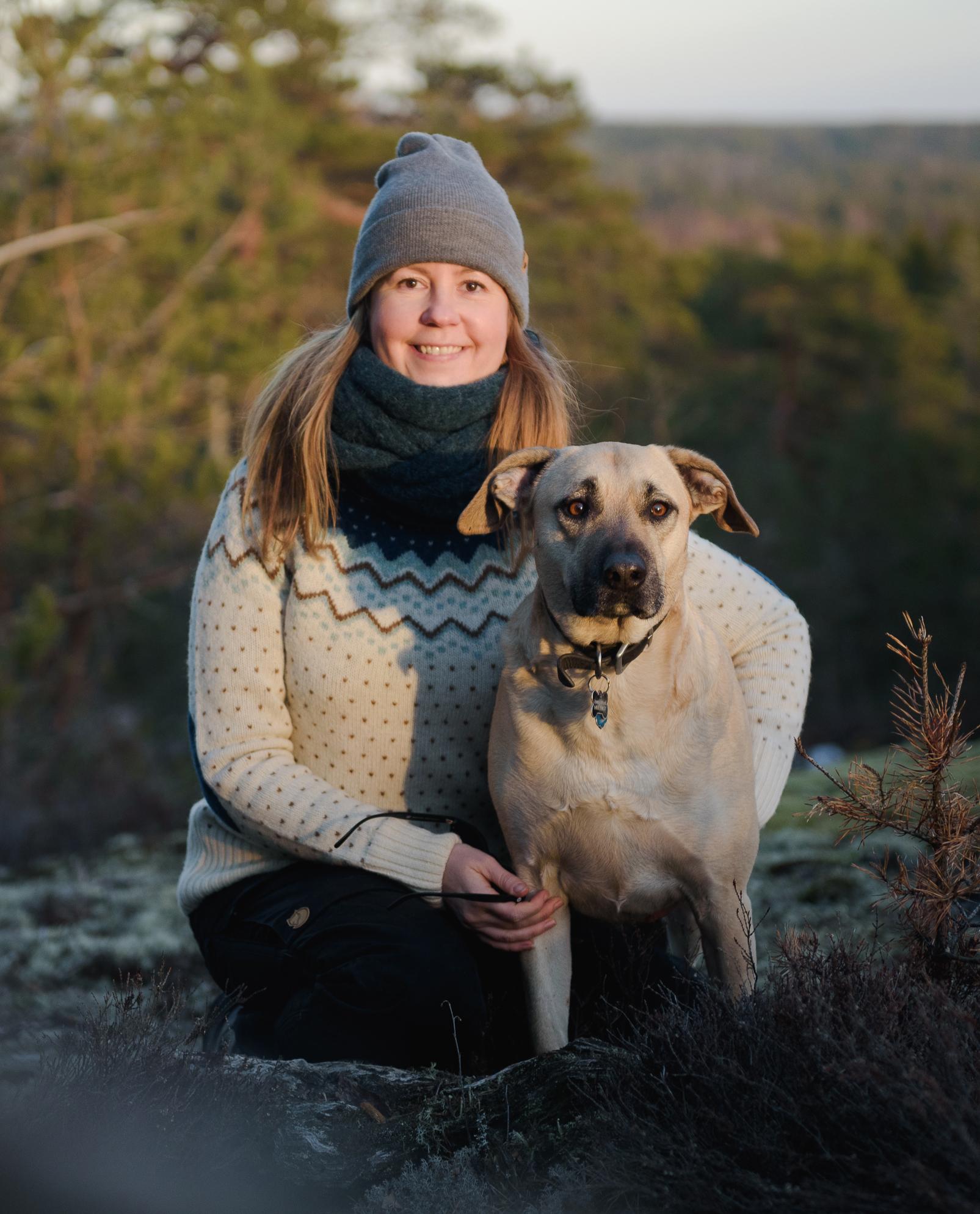 Jonna Wood, nainen kyykyssä kalliolla, vieressä vaalea koira