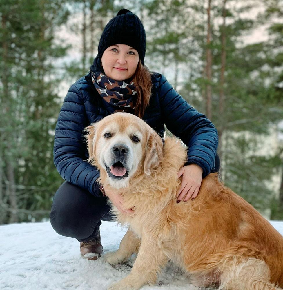 Janica Finneman, nainen kyykyssä metsässä, vieressä kultainennoutaja koira